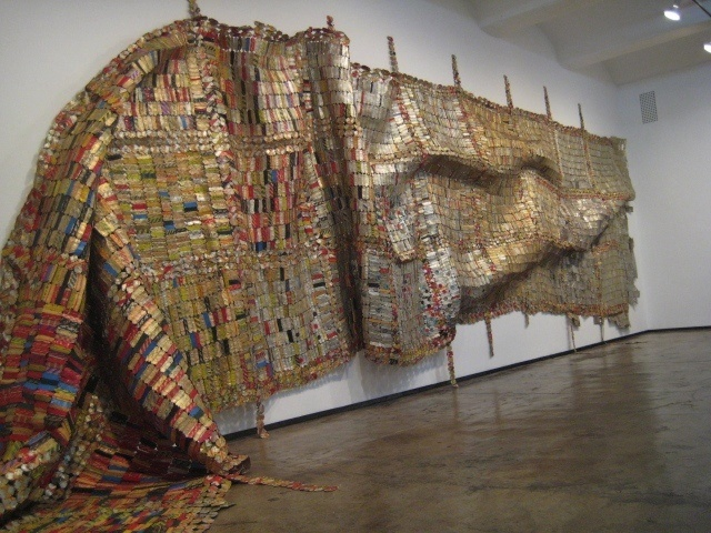 El Anatsui, woven metal, contemporary   A lot of his sculptures consist of recycled materials such as bottle tops, old graters, labels, copper wires and so on.