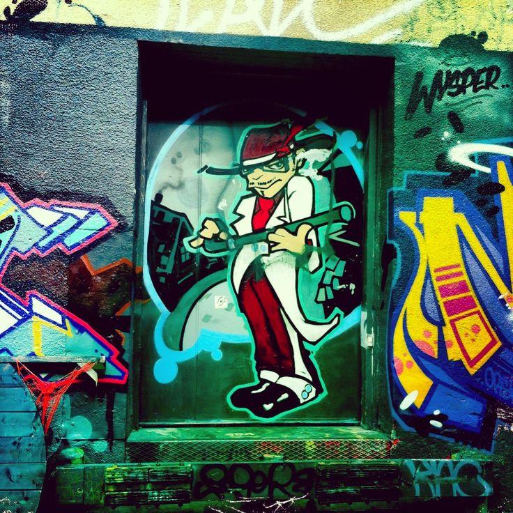 Spy in a delivery doorway. Toronto street art. Graffiti art.