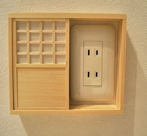 Tiny shoji screen covers unsightly outlets. DIY looks a little involved, but it's so cute.