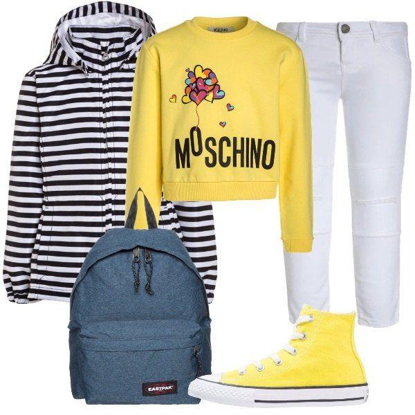 Un look per la scuola, tutto primaverile. Osserviamo: jeans skinny bianchi, felpa gialla Moschino, con stampa, giacca leggera a righe, con collo alla coreana e cappuccio, zainetto Eastpak e sneakers gialle alte Converse.
