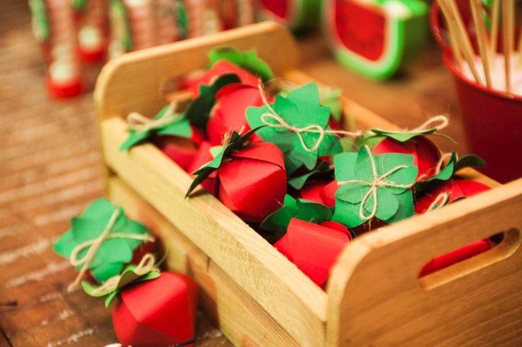 """O charmoso caixote de madeira enfeita a mesa da festa com pequenas caixas em formato de moranguinhos, cheios de confeitos de chocolate. A ideia é da Papel Charmoso (instagram.com/papelcharmoso), que produziu as caixas em """"scrapbooking"""" (uma técnica de arte em papel)"""
