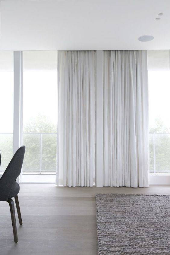 Floor to ceiling white drapes and oatmeal woven carpet for minimal, understated luxury via Rietveld Bouwprojecten | modern minimal urban living | did you know that Bemz offers customisable curtains in all our 250+ fabrics?!