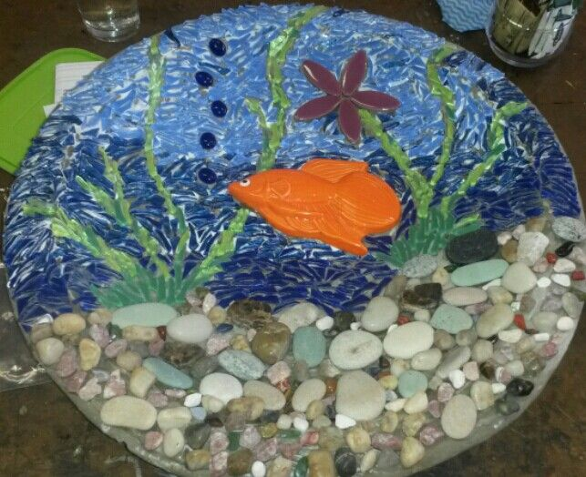 Bird bath with mosaic and pebbles.