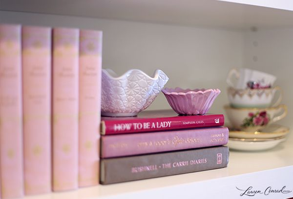 pretty pink bookshelves with candles and teacups