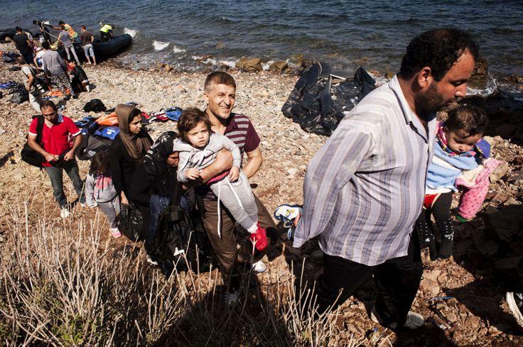 Los migrantes dejan la playa luego de llegar en botes inflables en la isla griega de Lesbos.