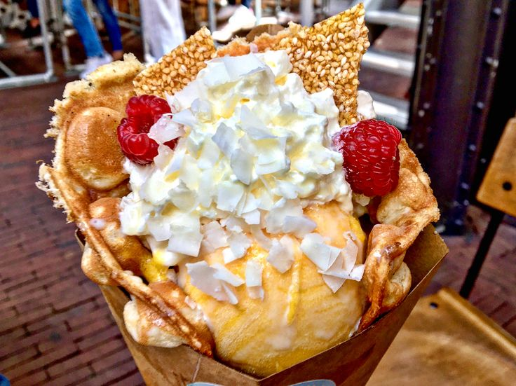 Mango ice cream, whipped cream, raspberries, coconut flakes and honey sesame brittle in an egg waffle.