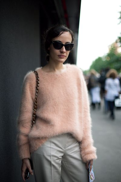 peach mohair sweater half tucked in beige trousers and sunnies with subtle cat eye, crossbody with chain handle
