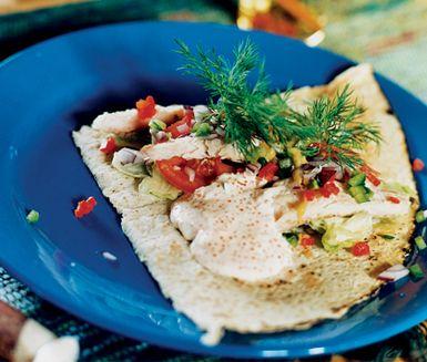 Jämtländsk wrap på tunnbröd med rökt fisk och kaviar är en lyxig rätt som serveras kall. Med en fräsch fyllning av paprika, dill, rödlök, sallad och tomat garnerar du wrapen med hovmästarsås och crème fraiche som blandats med röd kaviar.