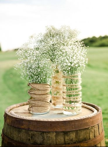These twine and burlap decorated vases look great for centerpieces for a rustic wedding. ~A