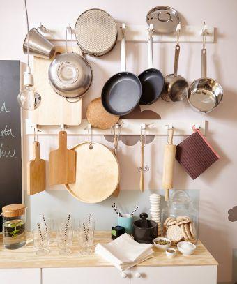 Nahaufnahme der Wand mit KUBBIS Leisten mit 7 Haken in Weiß, daran Töpfe, Pfannen und Kochutensilien.