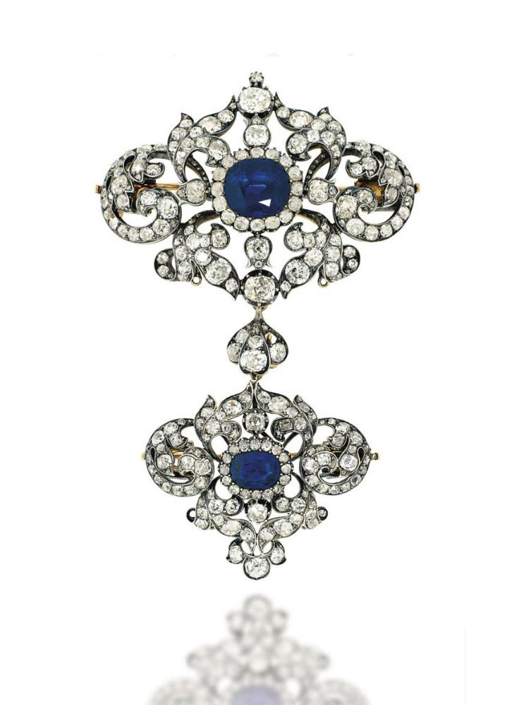A LATE 19TH CENTURY SAPPHIRE AND DIAMOND STOMACHER BROOCH. Composed of a pair of graduated cartouche shaped panels, each set with a central cushion shaped sapphire and old-cut diamond cluster, to a scrolling foliate surround similarly-set with old-cut diamonds throughout, mounted in silver and gold, circa 1880, 9.3cm long, brooch fittings detachable, one diamond deficient