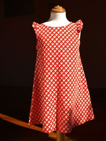 Tout Petit designed and made Liberty Tana Jersey Mc Evoy red dress.  Print of white watering can, on red background.  A-Line dress with cute wing sleeve, keyhole button at back.  95% cotton 5% elastane, made in Denmark.   Available in sizes 2 and 4 $109.95