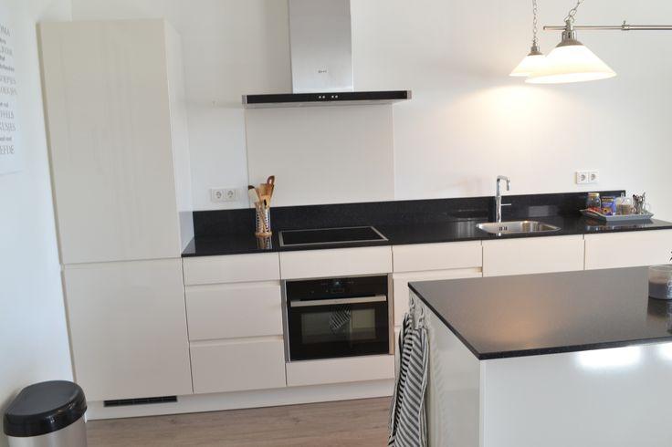 Witte hoogglans keuken zonder grepen met dun zwart werkblad.