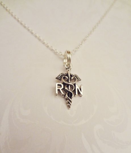 """RN Registered Nurse Necklace RN Registered Nurse Necklace, Earrings or Set with Caduceus Pendants with RN on them. Perfect Gift for RN Registered Nurse! This looks elegant, simplistic and awesome! Includes: -Silver Plated Caduceus Charms with RN on them. About the size of a dime. -Comes of a 16"""" Sterling Silver Necklace -Comes in a Box ready to Gift! Very Lightweight and These truly look amazing."""