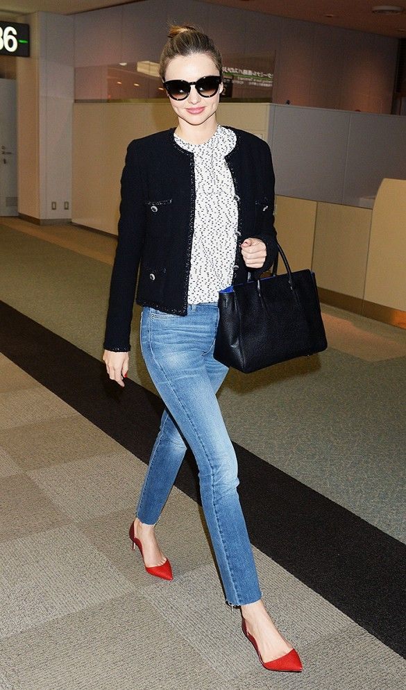 Miranda Kerr travels in a structured black jacket, sunglasses, and red pointy-toe flats