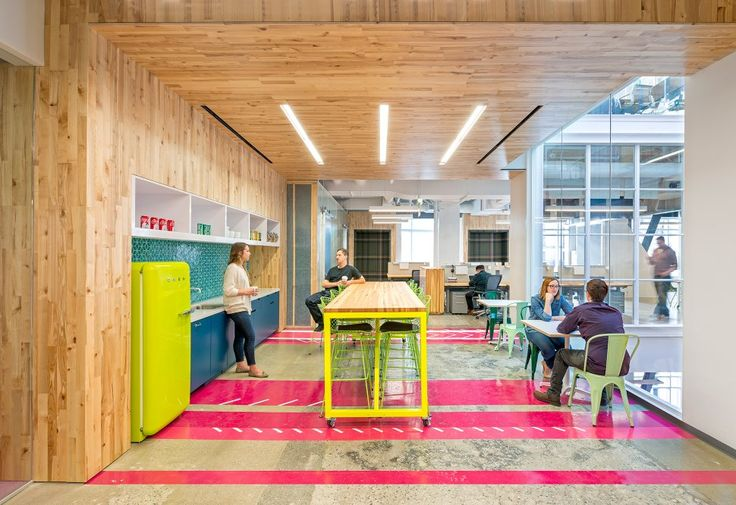 """Vibrant Spirit, Captured in Full Color The whimsy of this creative office extends into the communal kitchen, where a neon chartreuse refrigerator meets vibrant pink flooring and a sleek, wooden roof. Capital One Labs emphasized to Studio O+A that it wanted its """"wide open spirit"""" to be reflected in the common areas. Here, glass walls make the kitchen visually continuous with the rest of the office. CAPITAL ONE LABS"""