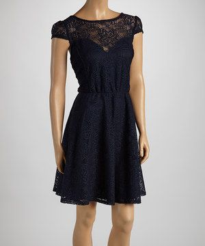 This frock features cap-sleeves and a lace overlay for a delicate, sophisticated effect. With a stately v-neckline covered in lace and a draped silhouette, it speaks to understated elegance.