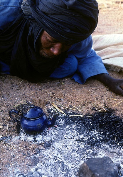 Sahara Morocco :)   Firewood, cut and brought across the Tenere, often runs low. Here, a caravaneer blows on embers to reheat some tea.
