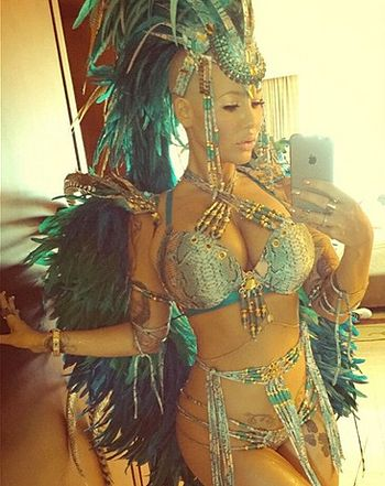 Amber Rose shared pictures of her tiny bikini and intense feather headdress at Carnival in Trinidad and Tobago, as well as a NSFW video of her grinding on an unnamed man -- watch now!