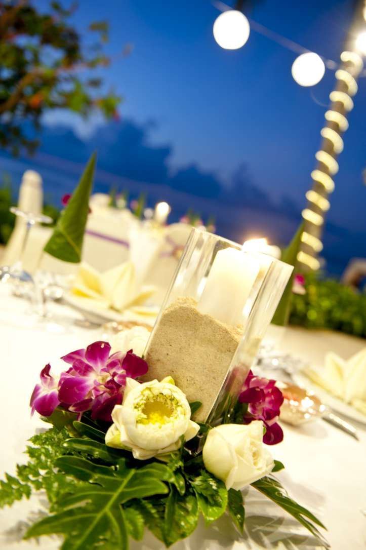 Tropical elegance - Purple orchids and white lotus flowers around a sand filled vase with candle.  Beach weddings, Koh Samui, Thailand
