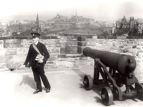 A photo from the Royal Mail Archive - a postman stands beside a cannon at Edinburgh Castle, 1934.