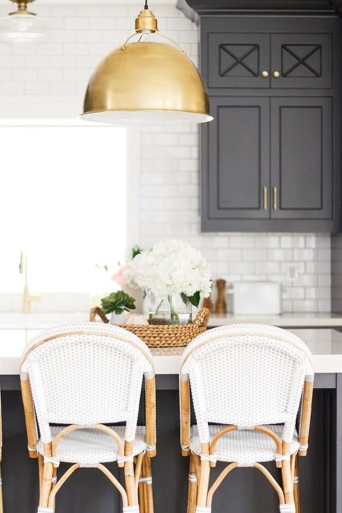 Serena & Lily Riviera Counter Stools sit at a white quartz countertop accenting a black center island lit by Eugene Large Pendants in this stunning black and white kitchen.