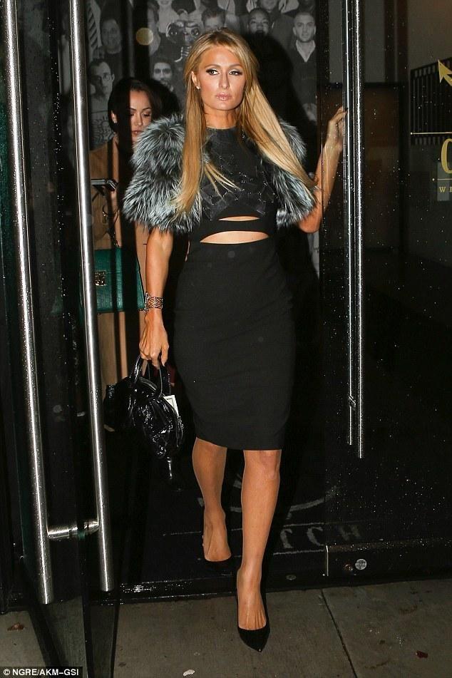 Paris Hilton wearing Yves Saint Laurent Patent Bow Bag in Black, Christian Louboutin Pigalle Follies Point-Toe Black Leather Pumps, Bowenero Bra and Lilly E Violetta Grey Fur Jacket