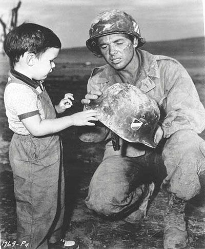 """Audie shows oldest son Terry a german World War II helmet  while off camera during the filming of TO HELL AND BACK."""""""