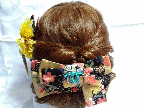 着物帯の変わり結び;枝垂れ桜結びを型どったヘアアクセサリーとダリアの花をセットにしたヘッドドレスです。着物帯結びを型どったアクセサリーは珍しく、和装の時には実際の帯結びと合わせてもお洒落感が増すのではないかと思います。枝垂れ桜柄に結び型も枝垂れ桜結びで合わせています。金色が艶やかな印象です。クリップを使用することで、ショートヘアにも飾って頂けると思います。共布でダリアのアーティフィシャルフラワーの髪飾りをセットにしています。成人式や卒業式、和装婚、パーティーなどを華やかで上品に彩ってくれると思います。着物帯結びアクセサリーは、和装はもちろんですが、普段の日常生活の中でも、差し色となり、普段遣いをして頂けると嬉しく思います。十分に気をつけておりますが、稀に接着剤のはみ出しがあるものが御座います。また、写真の撮り方により色彩のイメージが若干違う場合があります。ご了承の上、ご注文頂きますよう御願い申し上げます。