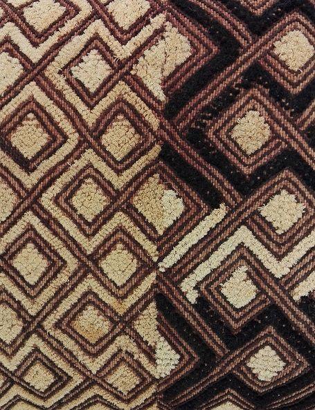 """I bellissimi tessuti degli Shoowa vengono chiamati """"velluti del Kasai"""" per il particolare tipo di lavorazione : la fibra della palma nana viene intrecciata e poi rasata con uno speciale coltello, ottenendo al tatto un risultato simile al velluto. Caratterizzati da disegni astratti, fondati su una complessa serie di simmetrie e intrecci, con un forte valore simbolico, i tessuti Shoowa costituiscono delle vere e proprie creazioni artistiche"""