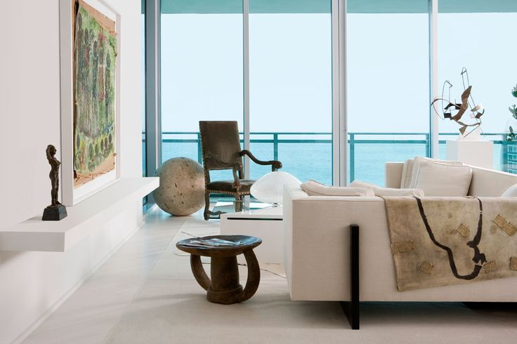 Darryl Carter . The living area of a Bal Harbour, Florida, condo designed by Darryl Carter features a custom-made sofa, an antique armchair, a mid-century iron sculpture, and a cocktail table by Brueton. A custom-made shelf holds a painting by Purvis Young and a sculpture by Claudio Barake, and the rug is from Stark. Interview: http://www.elledecor.com/home-remodeling/design-solutions/designer-darryl-carter-florida-condo
