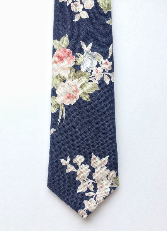 DESCRIPTION: This lovely mens skinny tie has been handmade using a beautiful blush pink floral print on navy blue linen. Please be aware that each tie purchased may vary, this is due to the large placement of the print. FABRIC: Linen. LINING FABRIC: Cotton. --------------------------------------------------------------------------------------------  DETAILS: • Made the traditional way with fabric cut on the bias • Each tie has canvas lining throughout • Fabric lining just at the tip on each…