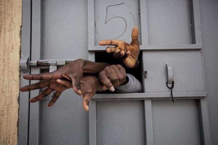 Trafic humain, Garabuli. Sub-Saharan illegal migrants and refugees reach through the window of a cell in the Garabuli Detention Centre, pleading for water, cigarettes, food and their release. Garabuli, Libya. (© Narciso Contreras)