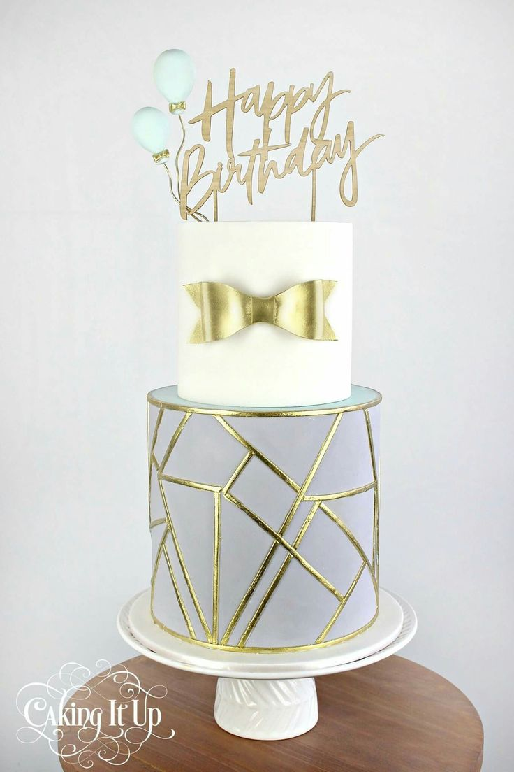 This modern geometric cake features asymmetric faceted shapes outlined in gold detail.
