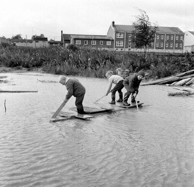 Til sjøs på land! Jomar, Oddmund og Arve så ikke problemet med at regnvannet ikke rant unna på Nordre Hallset. Problem liksom? Dette var jo gøy! (Adresseavisen 23. september 1966)