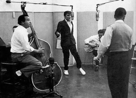"1954, Elvis Presley, working together for the first time in a recording studio with Scotty Moore and Bill Black, begins fooling around and plays an obscure 1946 Arthur Crudup song, 'That's All Right', during a break. Producer Sam Phillips asked them to refine their unique interpretation of the song and then recorded it. ""That's All Right"" became Presley's first release on Sun Records."