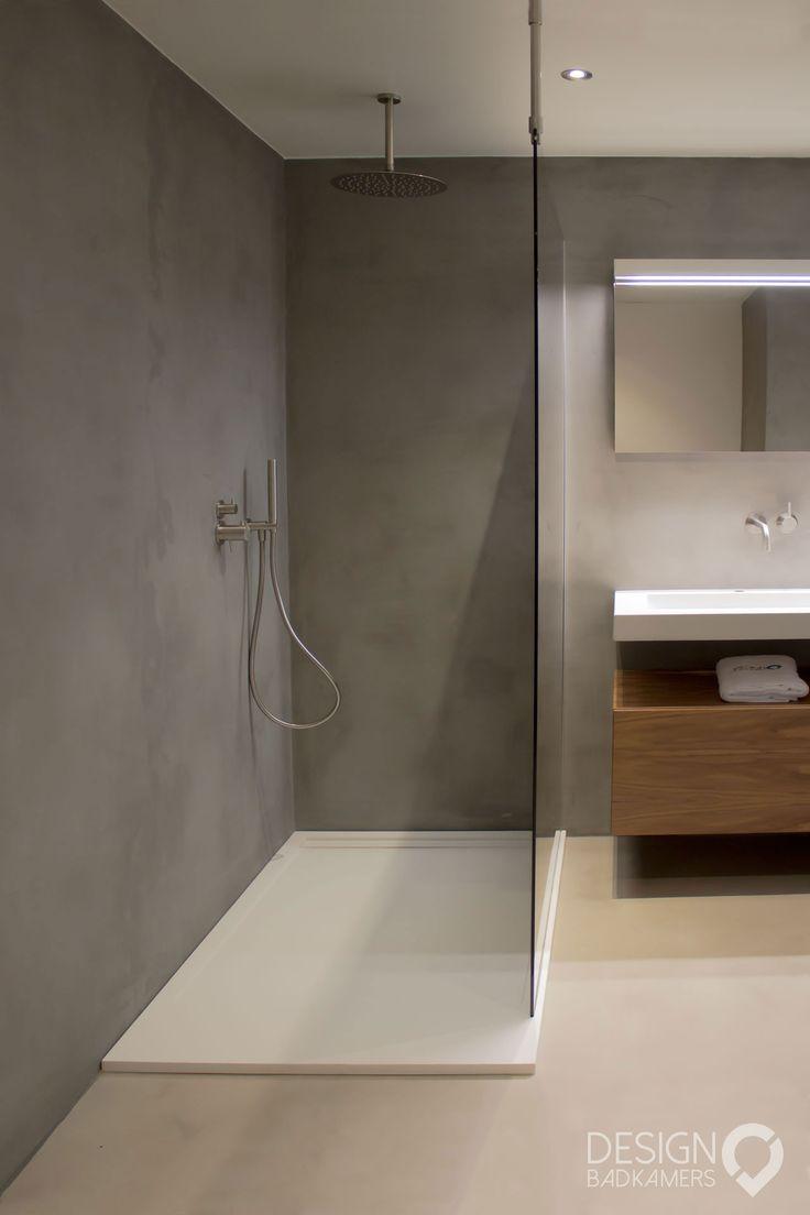 Maatwerk badkamer met gebruik van micro-beton (betonciré) op de vloer en muren voor een mooie beton-look, met RVS kranen en handdoekrek, een wastafel gemaakt van Solid Surface (Corian), spiegel met LED, en amerikaans noten badmeubel | #design_badkamers_breda #breda_design_badkamers