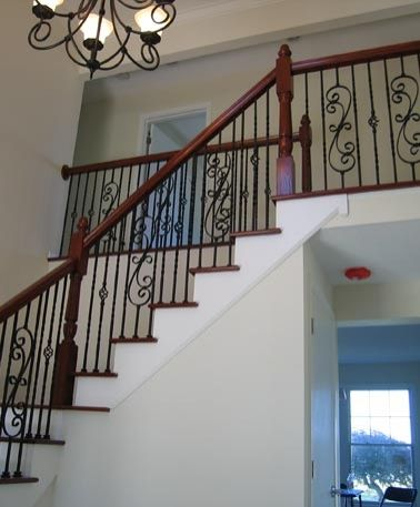 A staircase with Iron Spindles and Open Return Treads makes a statement in this home. Design by Great Lakes Stair & Millwork (Stair.com)