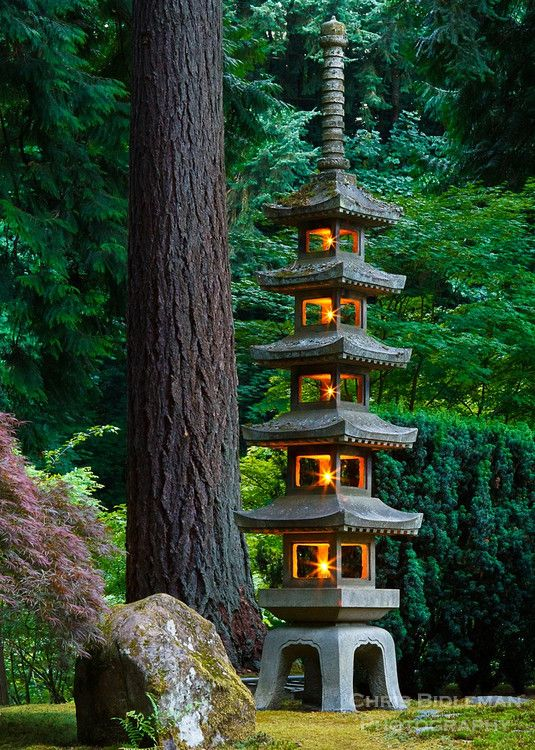 Photo by Chris Bidleman - The 18-foot Pagoda Tower stone lantern is lit in the Portland Japanese Garden. The five stories of the Pagoda are symbolic representing earth, water, fire, wind and sky. This lantern was given to Portland from its Sister City, Sapporo, Japan.