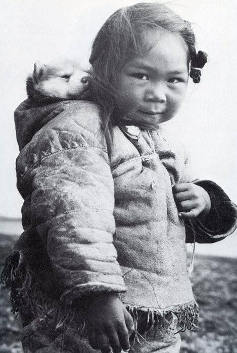 """Richard Harrington (1911-2005) fue un fotógrafo canadiense que realizó grandes reportajes sobre la vida en el Ártico.  Esta preciosa foto de una pequeña inuit llevando un cachorro de husky en su capucha la hizo sobre 1950 y la incluyó en su libro: """"El rostro del Ártico: la narración en palabras e imágenes de cinco viajes de un fotógrafo al lejano norte"""" (1952)"""