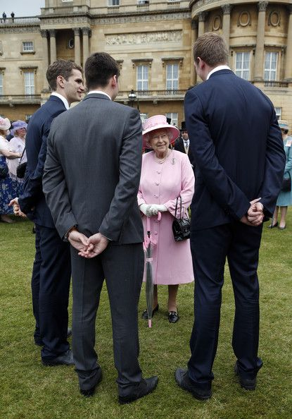 Queen Elizabeth II speaks to members of the Team GB Olympic Water Polo team (names not known)  during a garden party held at Buckingham Palace, on 30 May 2013 in London, England.
