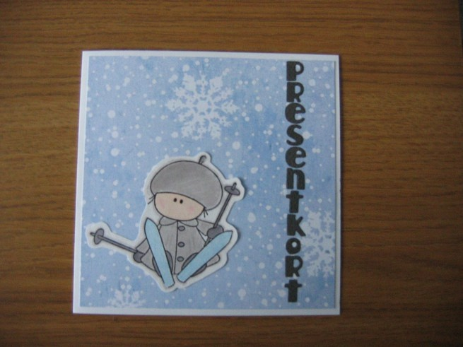 Kort som delades ut som presentkort på en skidlektion i fjällen.  Blått papper med snöflingor på, killen på skidor kommer från ett stämpelset från Panduro. Bokstäverna är utstansade med QuicKutz handstans.