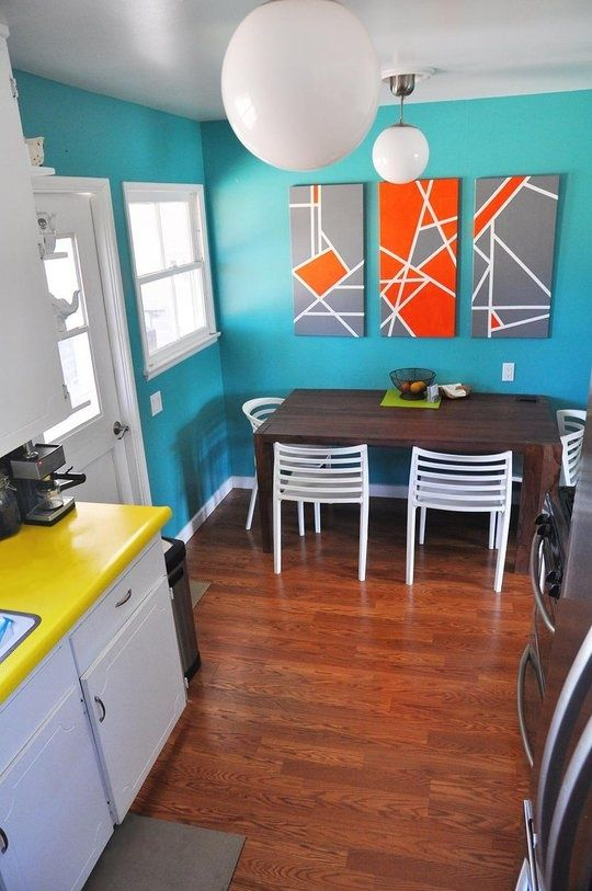 those paintings look like they could be a relatively easy DIY job w/ some canvases and painters tape....not to mention the orange and grey look awesome against the turquoise