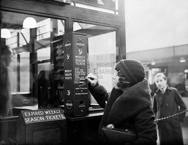 A traveller buys an underground season ticket from a vending machine at Highgate Station in 1932.