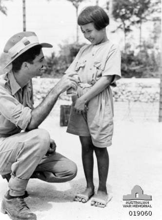 Morotai, Halmahera Islands. 1945. Dolly, a nine year old Japanese girl, is favourite at the Japanese prisoner of war (POW) camp at 1st Australian Compound, Morotai. Together with her parents she was captured on the West Coast of Borneo. Dolly is seen here chatting with an Australian soldier.
