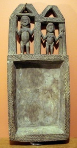 This Edo ceremonial object has two carved nude figures standing under arches, and a rectangular receptacle. The figures are fully carved front and back.