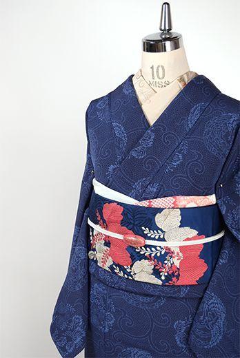 こっくりと深い濃紺と青の静謐な二色で染め出された粉雪のような細やかな点描に、典雅な鳳凰と花桐が形作る丸文様と優美な唐草が重ねられた正絹縮緬の袷着物です。