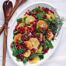 A festive orange, pomegranate, and spinach salad topped with a creamy orange-infused buttermilk dressing