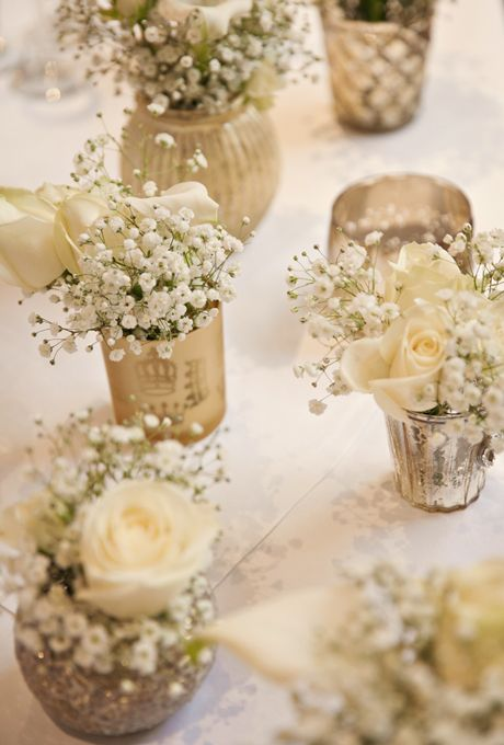 Brides.com: . Champagne and gold votives full of baby's breath and white roses serve as stylish accents to bedeck tables with.