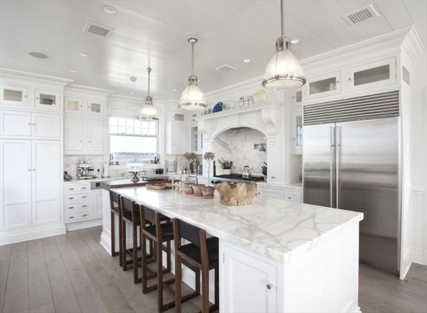 To me, what sets this kitchen in the Hamptons apart from the other all-white kitchens is the medium-dark floors. I think the painted wood ceiling could have been a nice soft color for better effect.